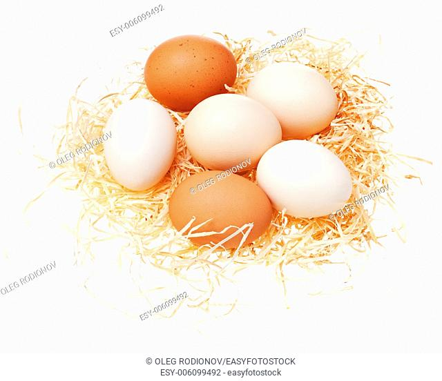 Eggs in straw nest isolated on white background