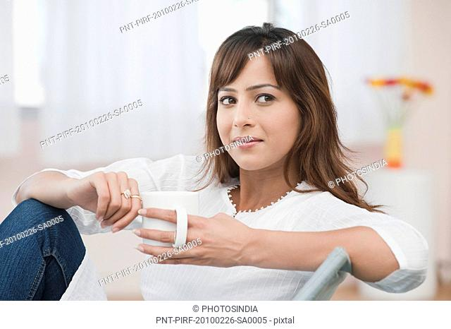 Close-up of a woman holding a cup of coffee and thinking