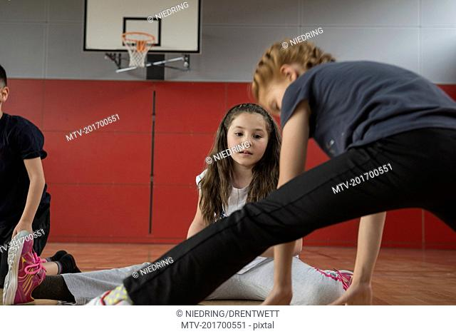 Girl amazed others by splitting her legs in sports hall, Munich, Bavaria, Germany