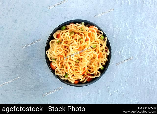 Instant noodles with carrot, scallions, and a sauce, a vegetable soba bowl, shot from the top on a slate background
