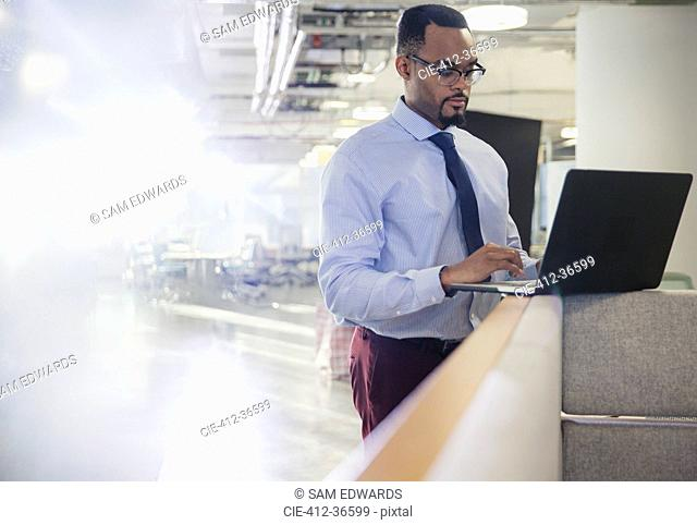 Businessman using laptop at office cubicle wall