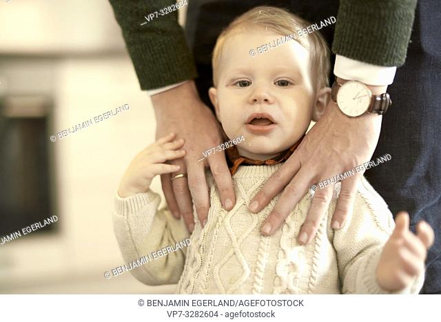 baby toddler child with hands of caring father on him, in Cottbus, Brandenburg, Germany