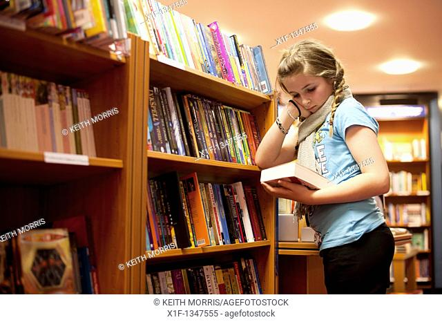 A twelve year old teenage girl reading in a bookshop, UK
