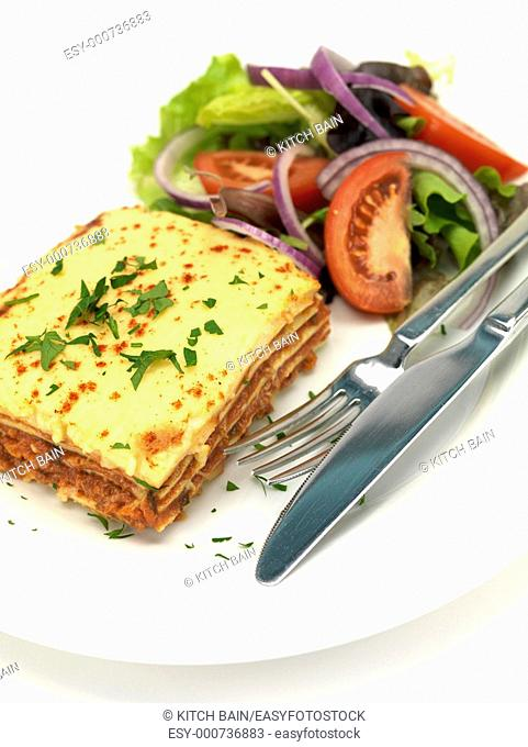 Lasagne plated up with a salad and isolated against a white background