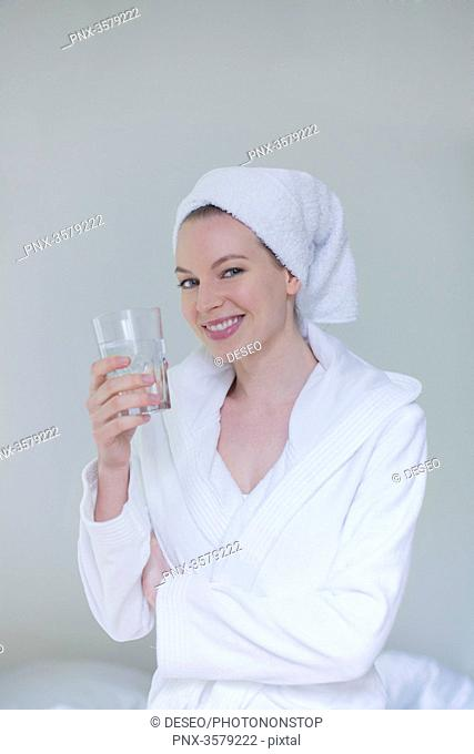 Woman in bathrobe with a glass of water smiling at camera