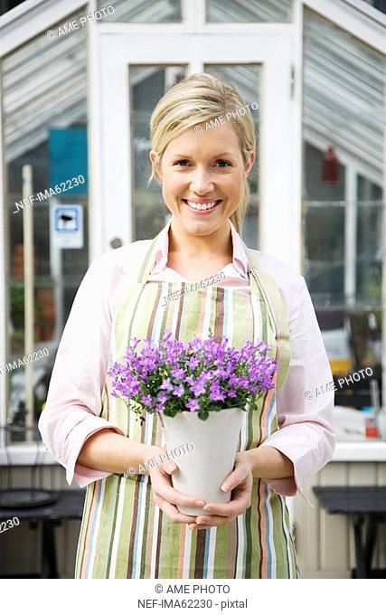 A blond woman working in a flower shop Sweden
