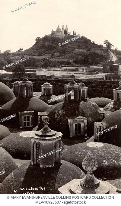 Picture of Cholula with the Great Pyramid in the background that looks like a natural hill. Only a very small part is uncovered and restored