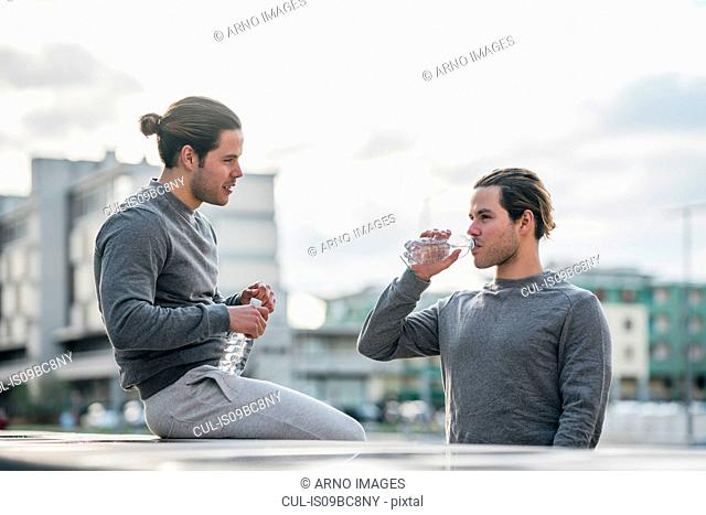 Young adult male twins taking a training break, drinking water