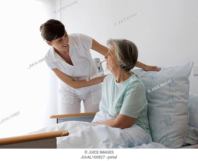 Nurse fixing patient's pillow in hospital