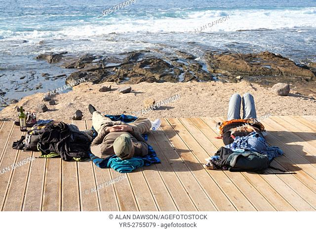 Backpacking couple relaxing on wooden boardwalk overlooking El Confital beach in Las Palmas on Gran Canaria, Canary Islands, Spain, Europe