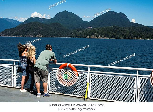 Passengers look out from the deck of a ferry boat from Langdale to Horseshoe Bay, BC, Canada