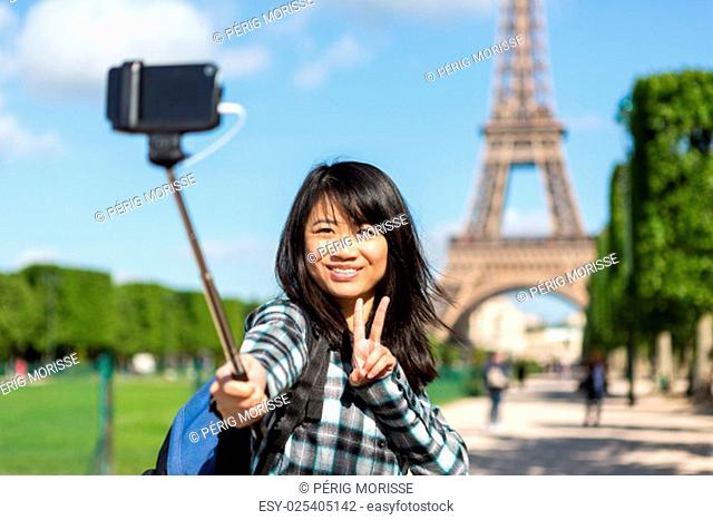 View of a Young attractive asian tourist in Paris taking selfie