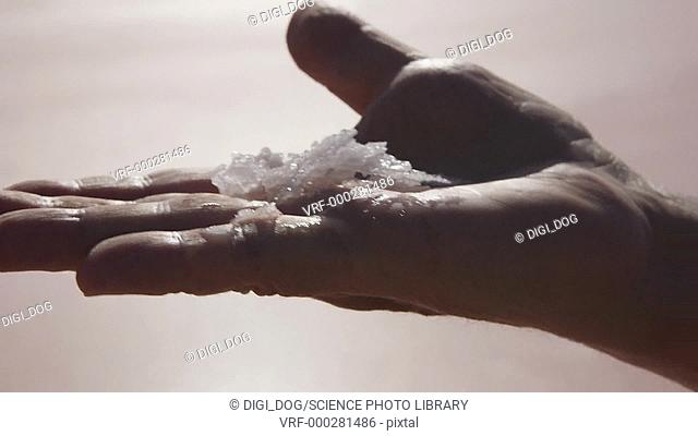 Person holding a small pile of sea salt that has been gathered from a reservoir
