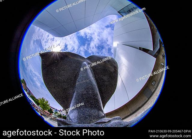 30 June 2021, Mecklenburg-Western Pomerania, Stralsund: A whale's tail fin sculpted from granite by artist Mile Prerad stands in front of the Ozeaneum (shot...