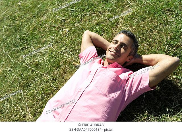 Man lying on grass with hands behind head and eyes closed