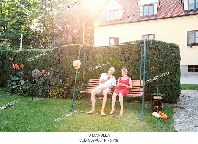 Senior couple, relaxing on swing seat in garden