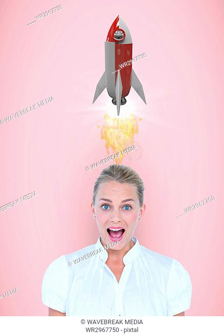 Portrait of shocked woman with rocket launch over head against pink background