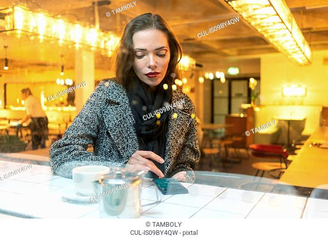 Young woman using smartphone in cafe, London, UK