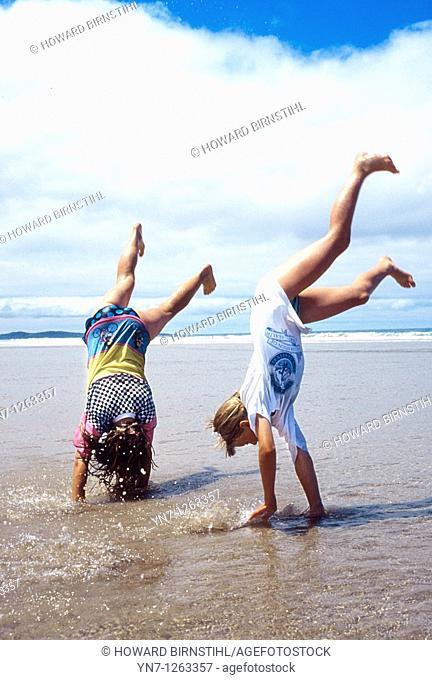 Kids somersalting on beach