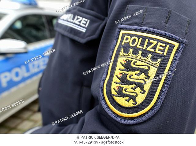 ILLUSTRATION - A the emblem of the police Baden-Wuerttemberg is seen on a policeman's jacket next to a police car in front of the police headquarters in...