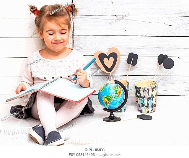 little cute girl school girl sits on a white wooden background with a globe in his hands and a notebook, the concept of knowledge