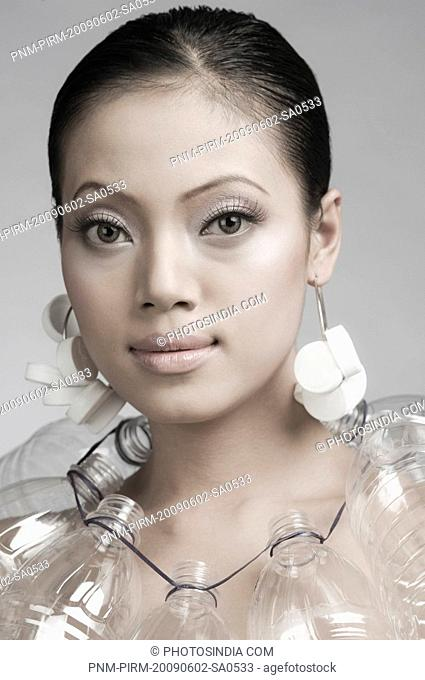 Female fashion model posing with neck ruff of plastic bottles and earrings of bottle caps