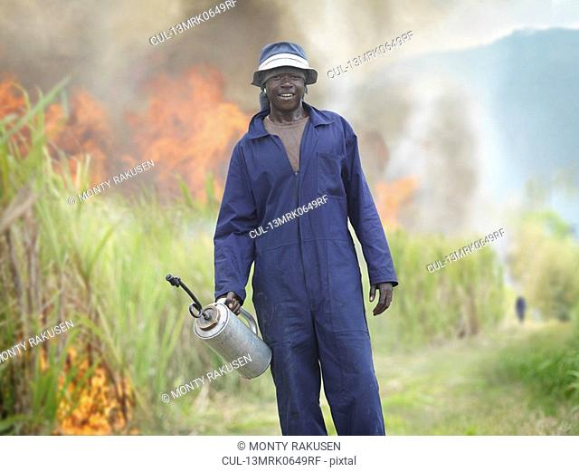 Worker In Sugar Cane Field With Fire