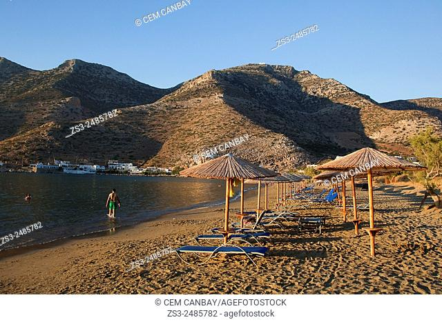 Thatched umbrellas on the beach near the port in Kamares at sunset, Sifnos, Cyclades Islands, Greek Islands, Greece, Europe