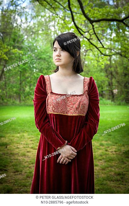 Young woman, standing in a park, wearing a long red vintage dress