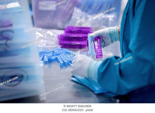Worker packing surgical instruments in clean room of surgical instruments factory, close up