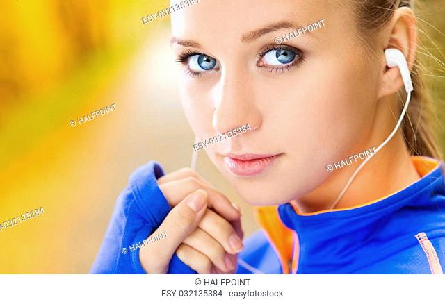 Sporty and active woman runner is listening to music before outdoor exercise