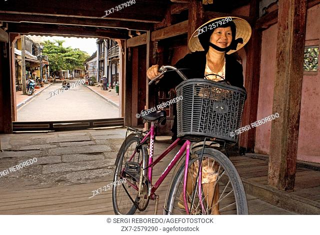 Old woman in a bicycle crossing the Japanese covered bridge in Hoi An, UNESCO World Heritage Site, Vietnam, Indochina, Southeast Asia, Asia
