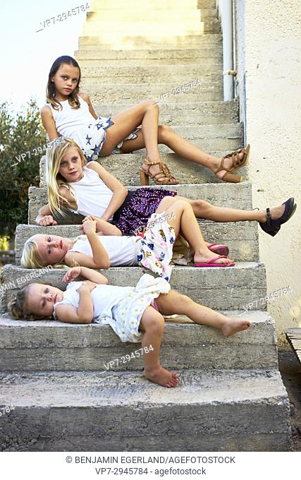 young girls laying on stairs outside in garden. Australian ethnicity. During holiday stay in Hersonissos, Crete, Greece
