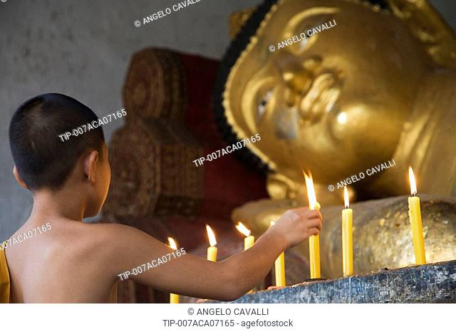 Thailand, Chiang Mai, Young Buddhist Monk lighting candle at Buddha statue in temple Wat Chedi Luang no property release