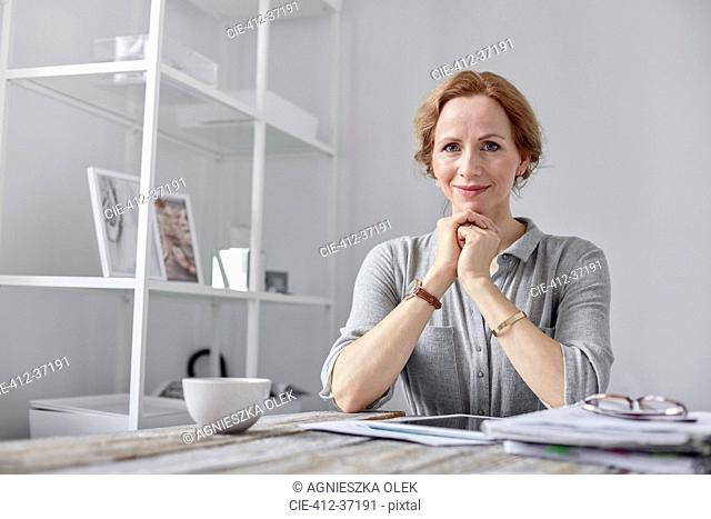 Portrait smiling, confident businesswoman using digital tablet and drinking tea in office