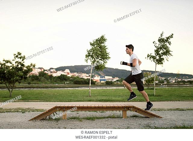 Athlete man running on an boardwalk, outdoors