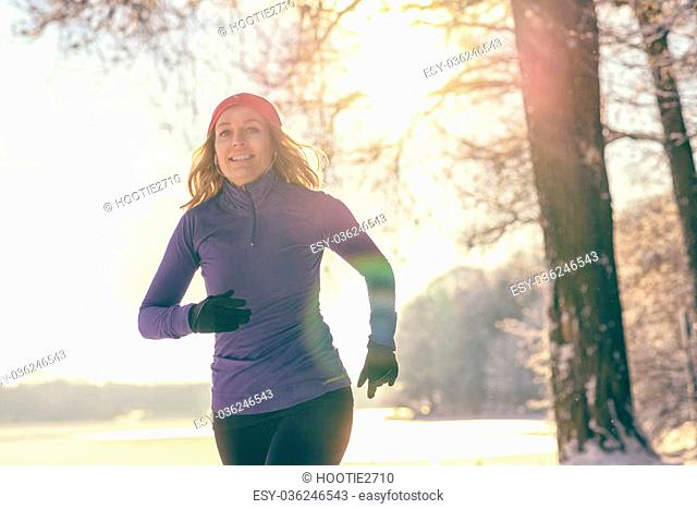 Full Body Shot of a Pretty Athletic Woman Jogging in winter with earphones and winter attire, Smiling at the Camera, with copy space