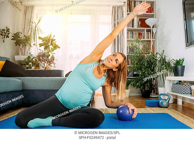 Pregnant woman doing pilates at home