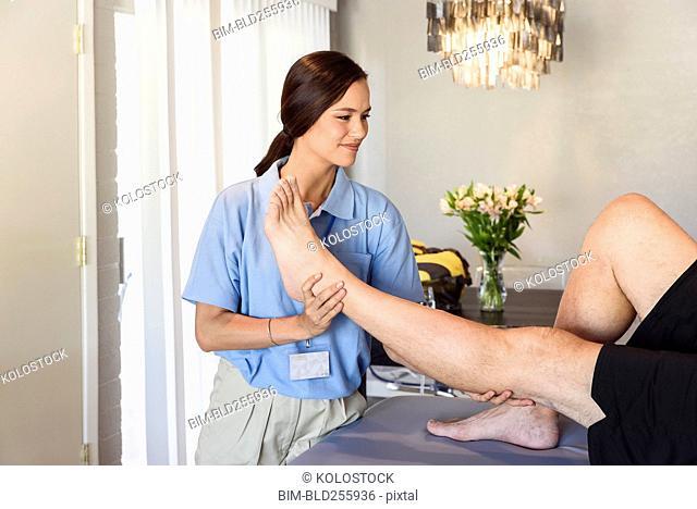 Physical therapist lifting leg of man