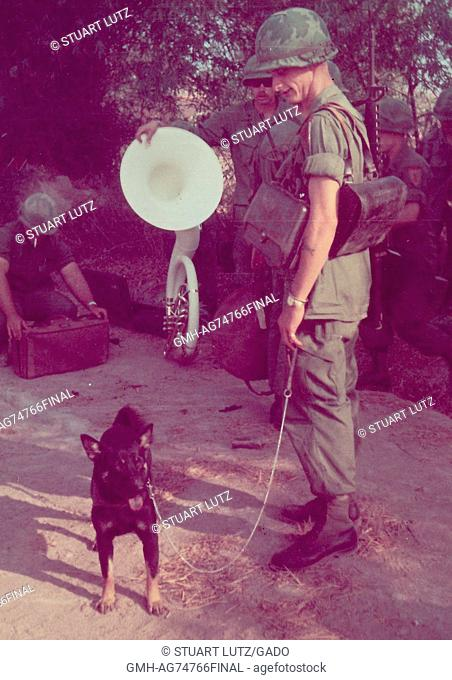A group of United States Servicemen in uniform are gathered together in a small group, one soldier has a dog on a leash while another soldier who is a member of...