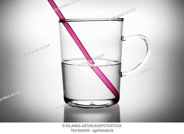 Taza de cristal con agua y pajita rosa