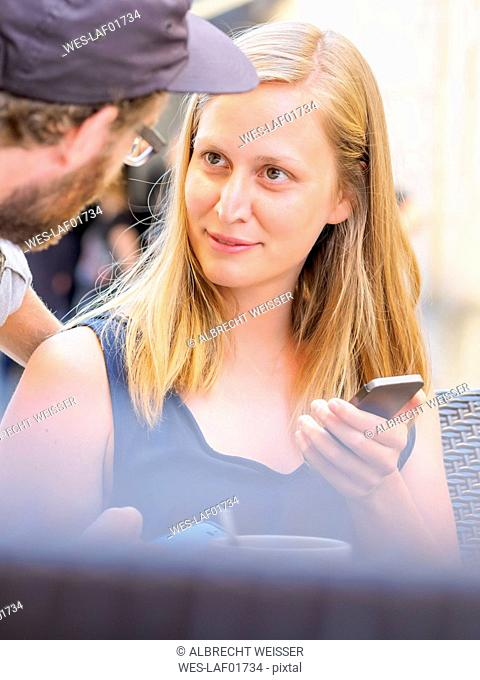 Portrait of blond young woman with smartphone face to face with her boyfriend