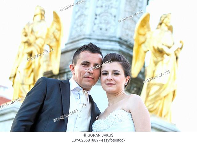 Newlyweds posing in front of the fountain of Virgin mary with four angels, leaning their heads and looking at the camera in Zagreb, Croatia