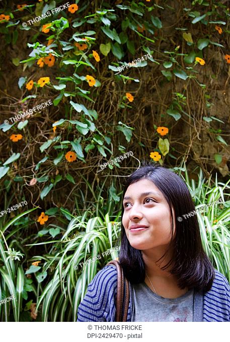 Portrait of a young mexican woman standing against a wall of flowers; San miguel de allende, Guanajuato, Mexico