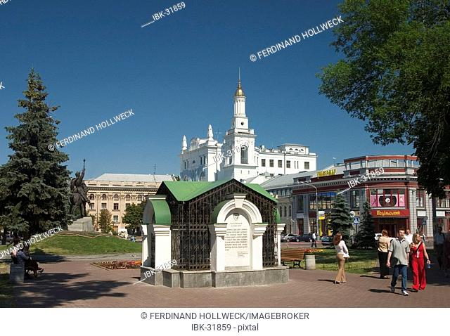 Ukraine Kiev district Podil Kontraktova Place oldest place of town park with spring and memorial of horseman with park visitors in background Pirohosci church...