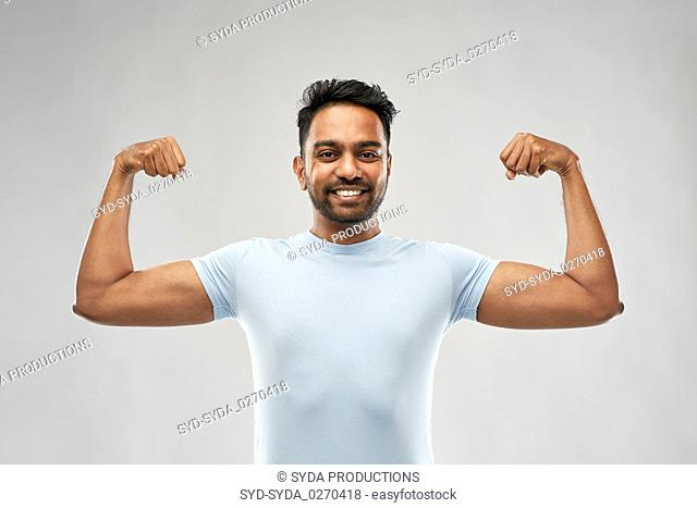 indian man showing biceps over grey background