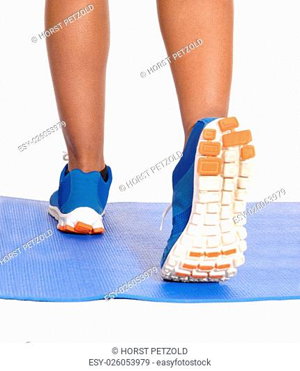 A closeup image of the sneakers and legs of a runner on a blue yoga mat.isolated for white background.
