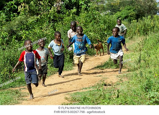 Happy boys running barefoot along dirt path, Kenya, June
