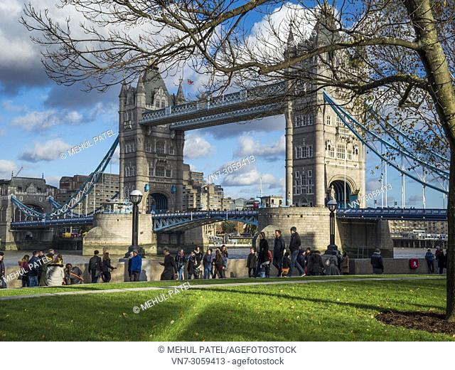 People walking along riverside walkway by Tower Bridge, London SE1, UK