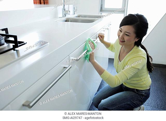 Young woman cleaning a kitchen and smiling